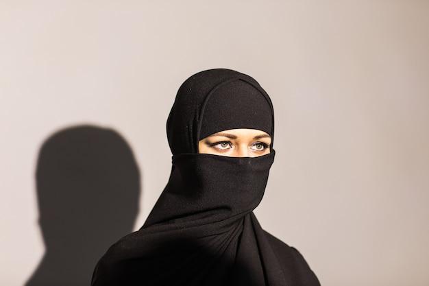 배경에 검은 색 niqab를 입고 젊은 여자.