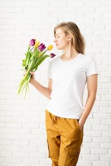 흰색 벽돌 벽에 포즈 튤립 꽃을 들고 빈 흰색 티셔츠를 입고 젊은 여자