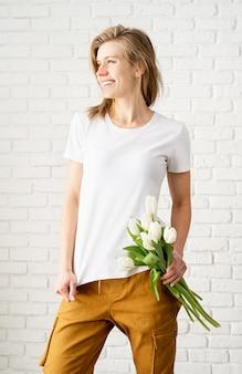 튤립 꽃을 들고 빈 흰색 티셔츠를 입고 젊은 여자.