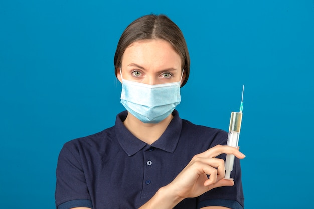 Молодая женщина, носить синюю рубашку поло в защитной медицинской маске, держа шприц, глядя на камеру с серьезным лицом, стоя на изолированных синем фоне