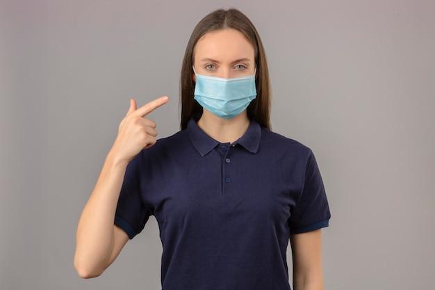 明るい灰色の背景に立っているカメラを見て深刻な顔をした彼女のマスクに指で指している防護医療マスクで青いポロシャツを着た若い女性
