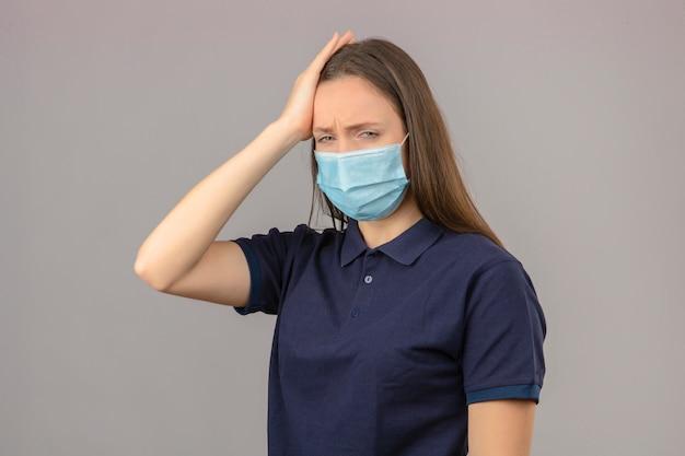 明るい灰色の背景に分離された頭の感覚の頭痛に触れる保護医療マスクで青いポロシャツを着た若い女性