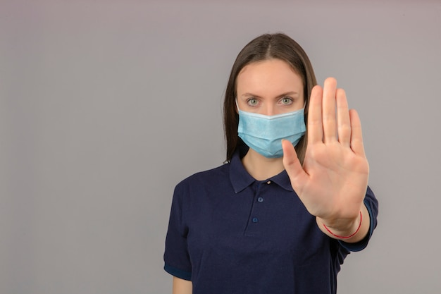 Young woman wearing blue polo shirt in protective medical mask showing hand stop gesture with serious face isolated on light grey background with copy space