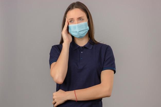 Giovane donna che porta la camicia di polo blu nell'emicrania di sensibilità della testa commovente della maschera medica protettiva isolata su fondo grigio chiaro