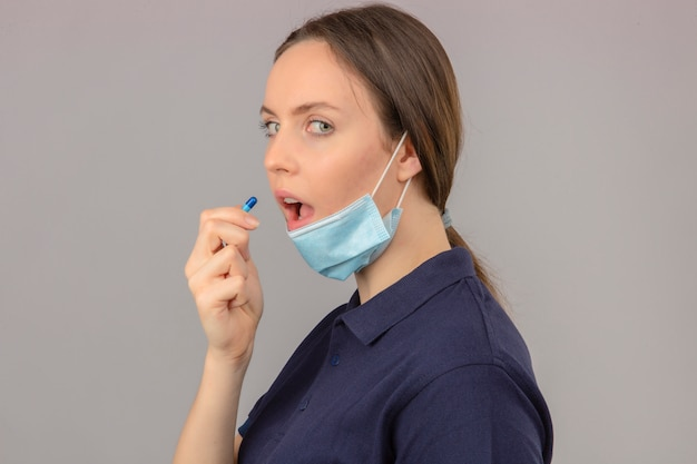 Young woman wearing blue polo shirt in protective medical mask with open mouth taking a pill on light grey background