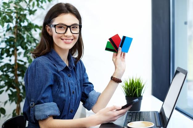 노트북과 커피, 프리랜서 개념, 작업 과정과 함께 카페에 앉아 파란색 셔츠와 안경을 착용하는 젊은 여자