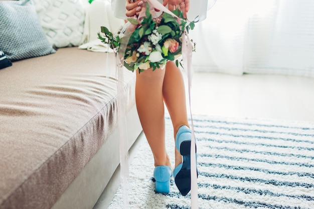 Young woman wearing blue shoes and holding bouquet at home