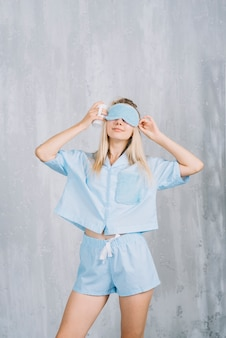 Young woman wearing blue sleeping eye mask in front of wall