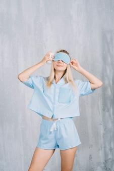 벽 앞에서 푸른 수면 아이 마스크를 착용하는 젊은 여자
