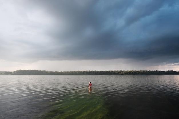 湖で泳いでいる明るいトップを着た若い女性。