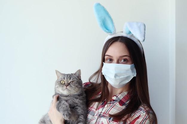 バニーの耳と猫を保持している防護マスクを着た若い女性