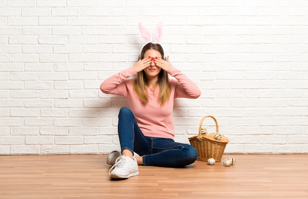 Young woman wearing bunny ears for easter holidays covering eyes by hands