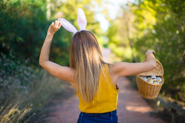 Young woman wearing bunny ears and with colorful easter egg at outdoors
