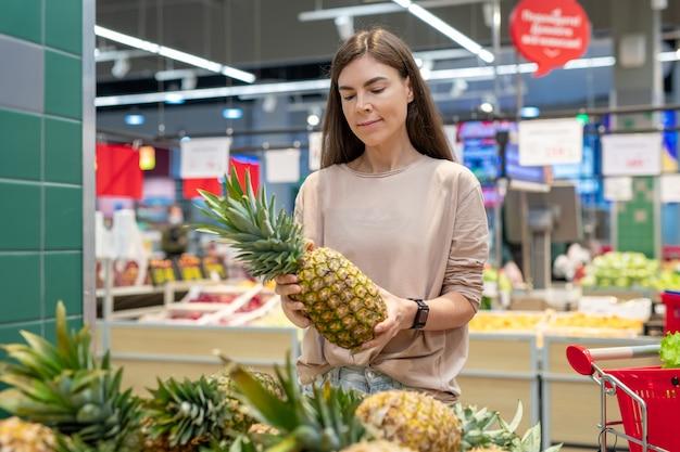 現代のスーパーマーケットで最高のパイナップルを選ぶカジュアルな服を着ている若い女性