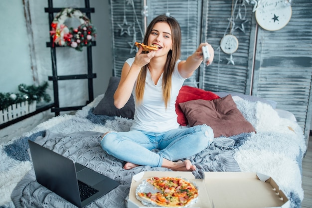 Young woman wearing at casual style sitting on bed with pizza and laptop and turns on the tv.