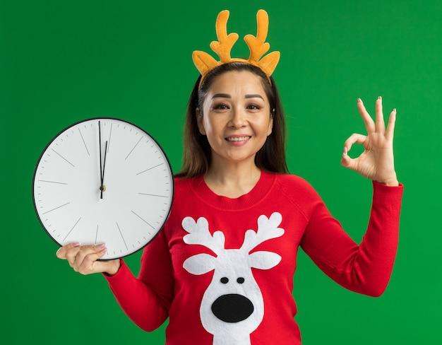사슴 뿔과 녹색 배경 위에 서있는 확인 서명을 보여주는 카메라를보고 웃 고 벽 시계를 들고 빨간 스웨터와 크리스마스 테두리를 입고 젊은 여자