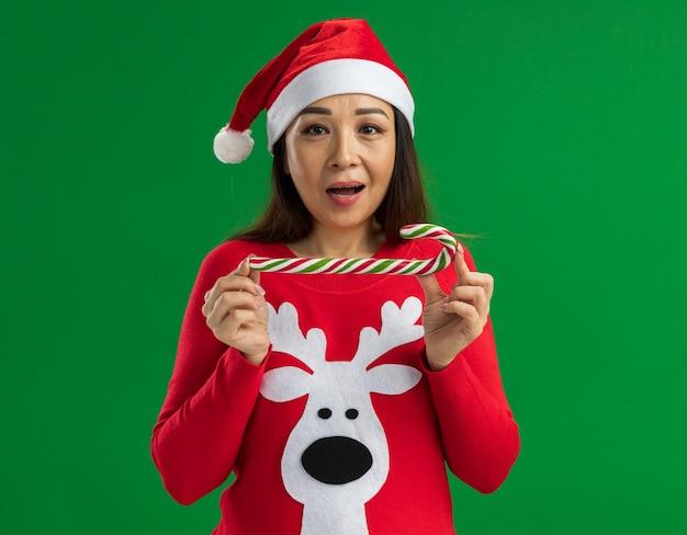 クリスマスのサンタの帽子と赤いセーターを着て、緑の背景の上に立って幸せで陽気なカメラを見てキャンディケインを保持している若い女性