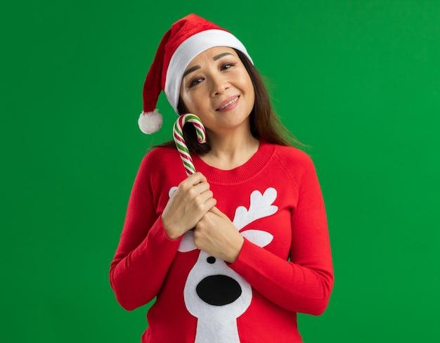 크리스마스 산타 모자와 녹색 배경 위에 서있는 얼굴에 미소로 카메라를 찾고 사탕 지팡이 들고 빨간 스웨터를 입고 젊은 여자