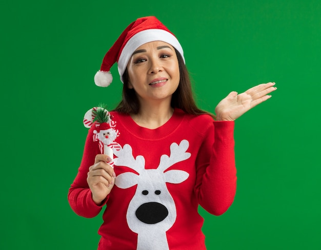 クリスマスのサンタの帽子と赤いセーターを着て、緑の背景の上に立って腕を上げて笑っているカメラを見てクリスマスキャンディケインを保持している若い女性