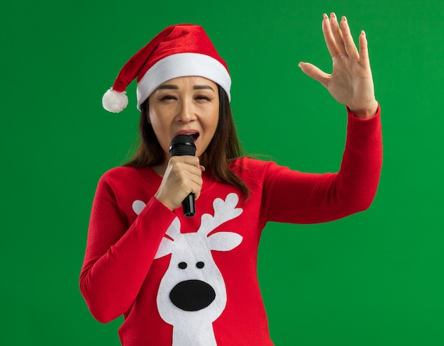 Молодая женщина в рождественской шляпе санта-клауса и красном свитере держит микрофон, поет счастливая и выходящая, стоя на зеленом фоне