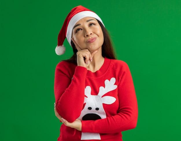 クリスマスのサンタの帽子と赤いセーターを着て、緑の背景の上に前向きに立って考えて見上げる若い女性