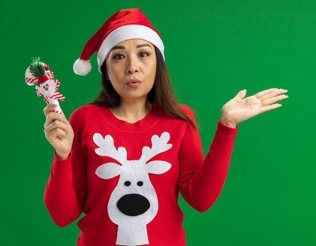 Giovane donna che indossa il cappello di babbo natale e maglione rosso che tiene il bastoncino di zucchero di natale che guarda l'obbiettivo confuso con il braccio alzato in piedi su sfondo verde