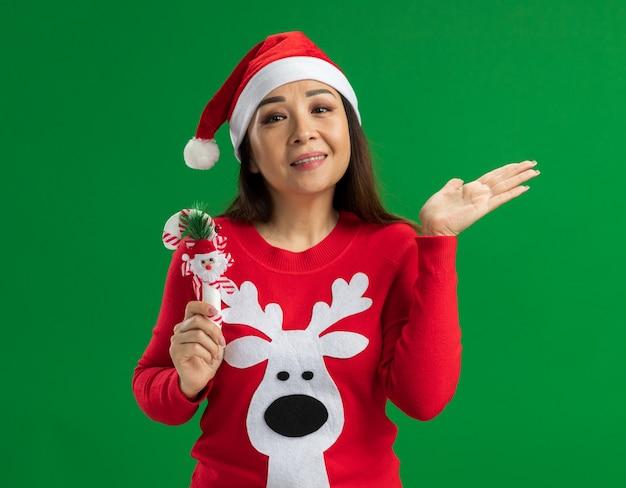 Giovane donna che indossa il cappello di babbo natale e maglione rosso tenendo il bastoncino di zucchero di natale guardando la fotocamera sorridente con il braccio alzato in piedi su sfondo verde
