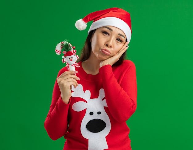 Giovane donna che indossa il cappello di babbo natale e maglione rosso che tiene il bastoncino di zucchero di natale che guarda l'obbiettivo con espressione triste in piedi su sfondo verde