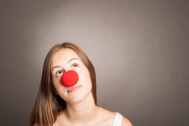 Young woman wearing a clown nose with copy space