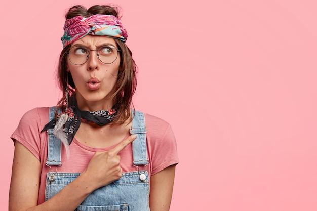 Молодая женщина в красочной повязке на голову и джинсовом комбинезоне