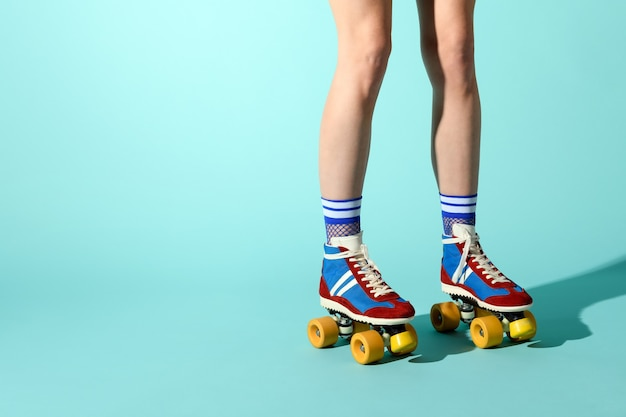 Young woman wearing colorful roller skates with sexy ankle high fishnet socks