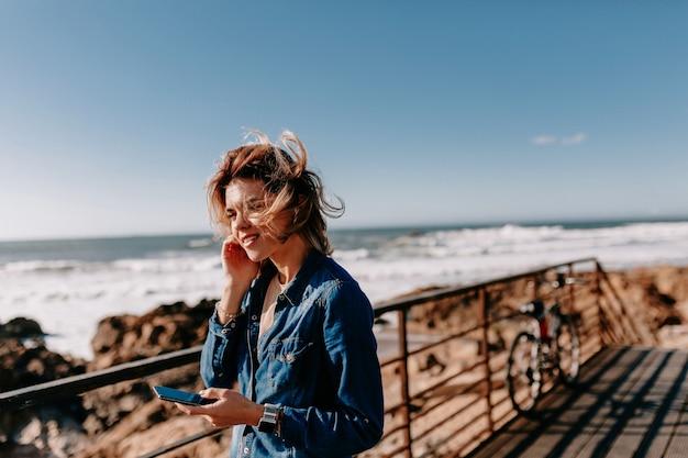 데님 셔츠를 입고 젊은 여자가 해변에서 포즈를 취하는 전화 통화