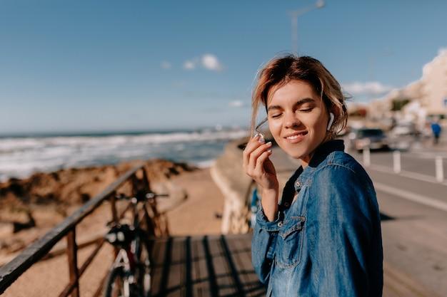 Молодая женщина в джинсовой рубашке с airpods на телефоне позирует на пляже