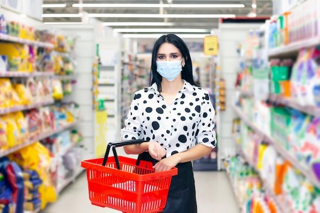 コロナウイルス肺炎の発生中にスーパーマーケットで買い物使い捨て医療マスクを着た若い女性