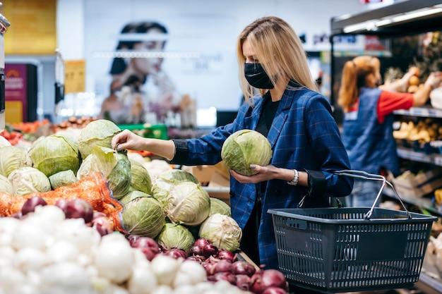 Молодая женщина в одноразовой медицинской маске делает покупки в супермаркете во время вспышки коронавирусной пневмонии