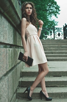Young woman wearing dress and walking on the street