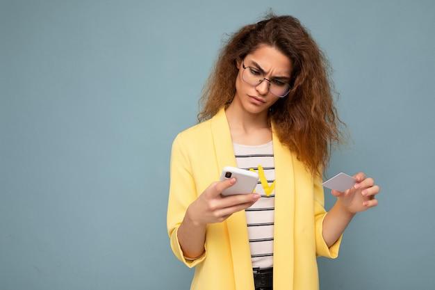 스마트폰 화면을 보고 신용 카드를 통해 온라인 쇼핑을 지불하는 전화와 신용 카드를 들고 배경 위에 격리된 일상적인 옷을 입고 젊은 여성.