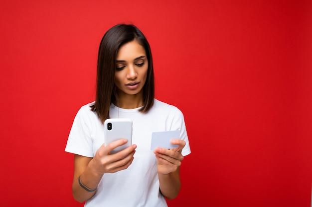 전화 및 신용 카드를 들고 배경 위에 절연 매일 옷을 입고 젊은 여자