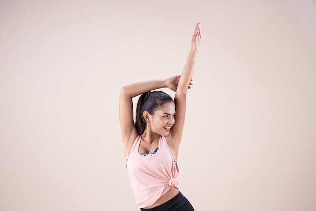 The young woman wearing exercise suit, raising hands up in the air, doing dance workout