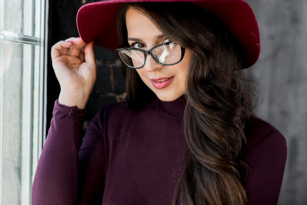 Young woman wearing eyeglasses holding hand on hat over her head