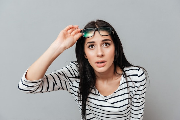 Young woman wearing eyeglasses shocked over grey surface. looking at front.