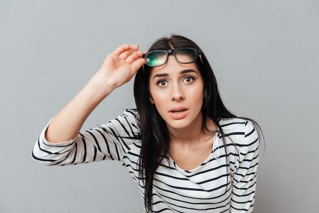 眼鏡をかけている若い女性は灰色の表面に衝撃を与えた。正面を見てください。