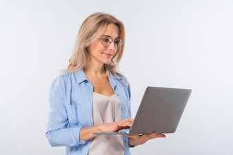 Young woman wearing eyeglasses using laptop against white background
