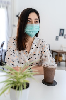 保護コロナウイルス(covid-19)のフェイスマスクを着用し、カフェでチョコレートミルクを飲む若い女性