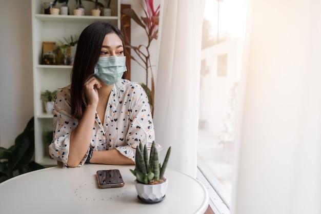 カフェでコロナウイルス(covid-19)を保護するためのフェイスマスクを身に着けている若い女性