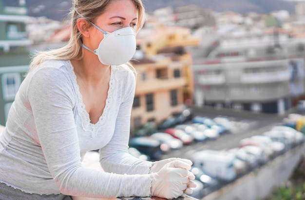 Young woman wearing face mask and gloves for coronavirus prevention - stop spreading covid 19 concept - focus on hands