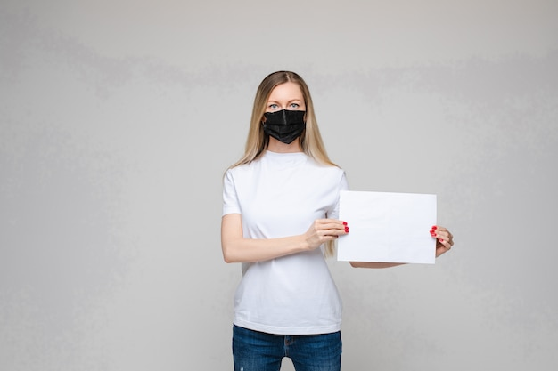 Young woman wearing face mask holding blank sign