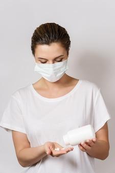 얼굴 마스크를 착용하는 젊은 여자는 흰색 알 약을 들고있다