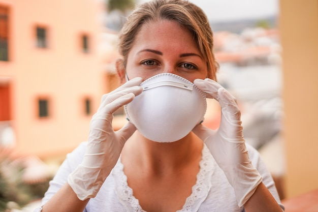 Young woman wearing face mask and latex gloves for coronavirus prevention -  stop spreading covid 19 concept - focus on hands