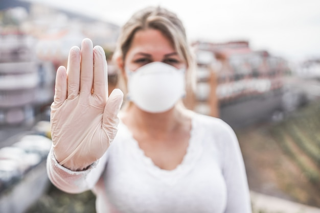 Young woman wearing face mask and latex gloves while showing stop hand gesture for coronavirus prevention -  stop spreading covid 19 concept - focus on hand